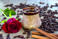 Cup of black coffee with coffee beans, red rose . Cup of black coffee with coffee beans, red rose, coffee beans, on sackcloth Royalty Free Stock Photography