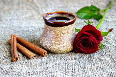 Cup of black coffee with coffee beans, red rose . Cup of black coffee with coffee beans, red rose, on sackcloth Royalty Free Stock Images