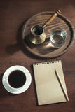 Cup of black coffee, copper cezve and water in a glass on wooden tray in vintage style. View from above. Stock Images