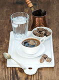 Cup of black coffee, copper pot, water with ice in glass and cane sugar cubes on white ceramic serving board over rustic Royalty Free Stock Image