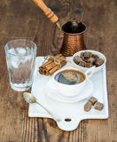 Cup of black coffee, copper pot, water with ice in glass, cinnamon sticks and cane sugar cubes on white ceramic serving Stock Photos