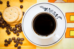 A cup of black coffee, crackers and coffee beans Stock Photo