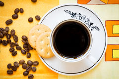A cup of black coffee, crackers and coffee beans Royalty Free Stock Images