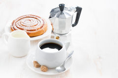 Cup of black coffee, cream, sweet bun and coffeemaker Royalty Free Stock Photo