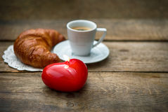 Cup of black coffee with croissant and red heart candle Royalty Free Stock Photo