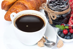 Cup of black coffee, croissants, jam and berries Royalty Free Stock Photography