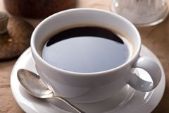Cup of Black Coffee. A cup of delicious fresh black coffee on a rustic table top stock photo