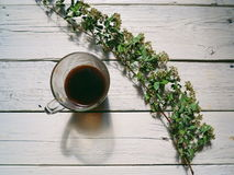 A cup of black coffee and a dry branch with flowers on white boards Royalty Free Stock Image