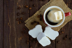 A cup of black coffee (espresso) and sweet marshmallow on a dark wooden background Royalty Free Stock Images