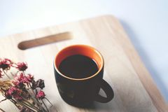 Coffee and flower. A cup of black coffee  and flower on wooden board Royalty Free Stock Images