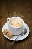 Cup of black coffee with foam and cane sugar cubes Royalty Free Stock Photo
