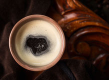 Cup of black coffee with foam on dark wooden background, top view Royalty Free Stock Image