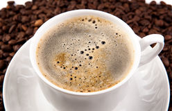 Cup of black coffee with foam. And roasted coffe beans close-up Royalty Free Stock Photos