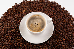 Cup of black coffee with foam. And roasted coffe beans close-up Stock Photos
