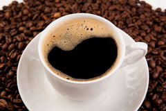 Cup of black coffee with foam. And roasted coffe beans close-up Royalty Free Stock Image