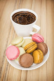 Cup of black coffee with french colorful macarons, sweet delight Royalty Free Stock Photos
