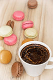 Cup of black coffee with french colorful macarons, sweet delight Royalty Free Stock Images