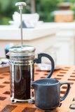 Cup of black coffee and french press on table at restaurant Stock Photography