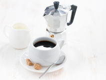 Cup of black coffee, fresh cream and coffeemaker Stock Photo