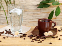 Cup of black coffee and a glass of cold water Stock Images