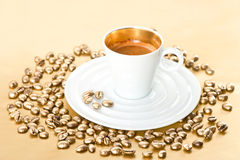 Cup of black coffee with golden coffee beans Stock Photo