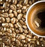 Cup of black coffee with golden coffee beans Stock Photos
