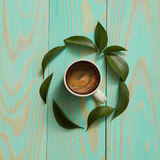 Cup of black coffee. And green leaves isolated on blue background. Flat lay Royalty Free Stock Photography