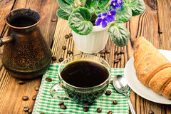 Cup of black coffee on green napkin with croissant, turkish coffee pot, flower pot, wooden table in cafe Royalty Free Stock Images
