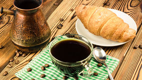 Cup of black coffee on green napkin with croissant, turkish coffee pot, wooden table in cafe Stock Image