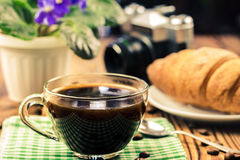 Cup of black coffee on green napkin with croissant, vintage camera, flower pot, wooden table in cafe. travel concept Royalty Free Stock Photography