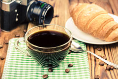 Cup of black coffee on green napkin with croissant, vintage camera, wooden table in cafe. travel concept Royalty Free Stock Image