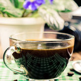 Cup of black coffee on green napkin, vintage camera, flower pot, wooden table in cafe. travel concept Stock Photos