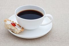 Cup of black coffee with half a small cake Royalty Free Stock Image