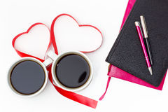 Cup of black coffee, a heart from red ribbon, diaries and pens on a white background. Stock Photo