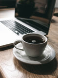Cup of Black Coffee Beside Laptop Stock Photos