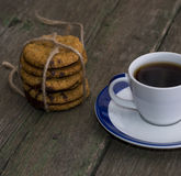 Cup of black coffee and linking of cookies on the old desktop Royalty Free Stock Images