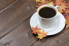 Cup of black coffee and maple leaves Stock Images