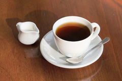A cup of black coffee and milk on table. A cup of black coffee and milk on wooden table Stock Image