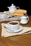 A cup of black coffee with a milkman with. Pies on a tray with newspaper Royalty Free Stock Photography