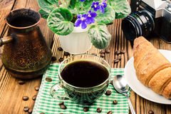 Cup of black coffee on napkin with croissant, turkish coffee pot, vintage camera, flower, wooden table, travel concept Stock Photos