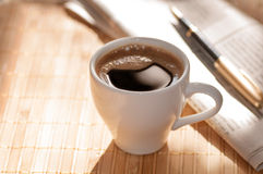 Cup of black coffee, newspaper and a pen against Royalty Free Stock Images