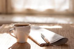 Cup of black coffee, newspaper and a pen against Royalty Free Stock Photos
