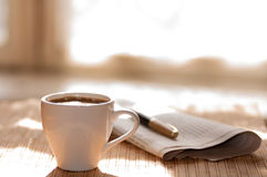Cup of black coffee, newspaper and a pen against Stock Photo