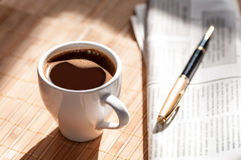 Cup of black coffee, newspaper and a pen Stock Photography