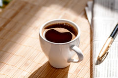 Cup of black coffee, newspaper and a pen Royalty Free Stock Photography