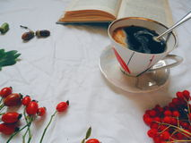 Cup of black coffee and open book on white cloth Stock Images