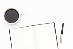 Cup of black coffee, open the diary and pen on a white background. Minimal business concept. Flat lay. Top view Royalty Free Stock Photography