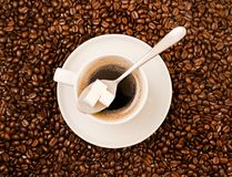 Cup of black coffee over bean covered background. Cup of fresh black coffee with a spoon full of sugar shot from above over roasted bean covered background Royalty Free Stock Image