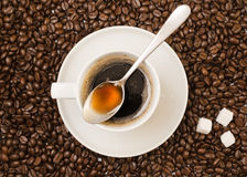 Cup of black coffee over bean covered background Stock Photos