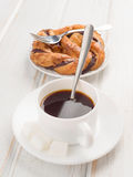 Cup of black coffee with pastry loop on wood Stock Image